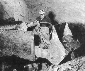 A miner loads a tram car with iron ore.