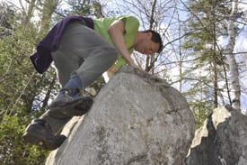 Alan climbs to the top of a large boulder along the trail.