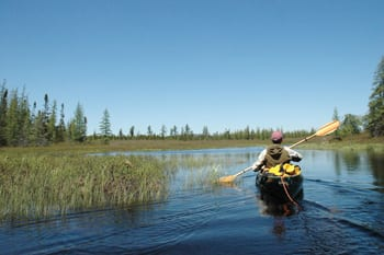 Phil Brown paddles through private land toward Lake Lila.