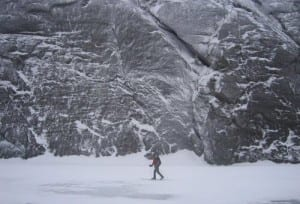A skier crosses Avalanche Lake near the cliffs of Mount Colden.