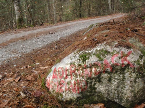 "The words ""Adirondack Homeland"" appear on a boulder at the entrance to the Pharaoh Lake Wilderness, a reminder of the battle over Crane Pond Road two decades ago. Photo by Phil Brown."