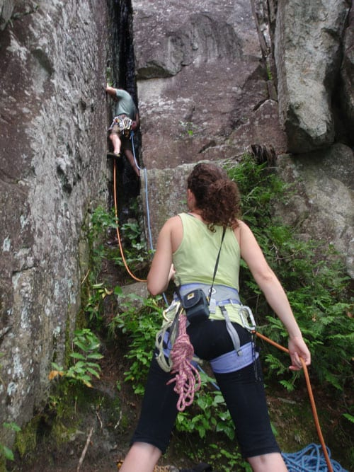 Jecinda Hughes belays Josh Wilson as he begins the ascent of the chimney on Hurricane Crag. Photo by Phil Brown.
