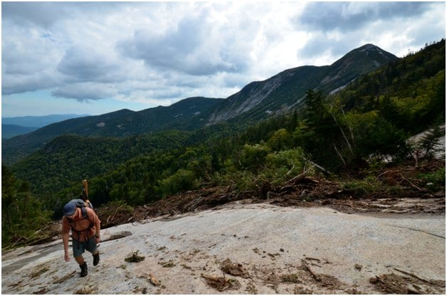 A hiker climbs a new slide on Saddleback Mountain the day after Hurricane Irene. Photo by Brendan Wiltse.