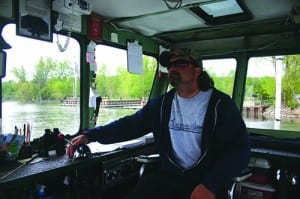 Ferry owner Michael Matot handles the throttle while cables take care of steering.