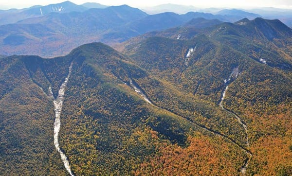 The aerial photo shows slides on Lower and Upper Wolf Jaw mountains that were created or enlarged by Tropical Storm Irene. Photo by Kevin MacKenzie