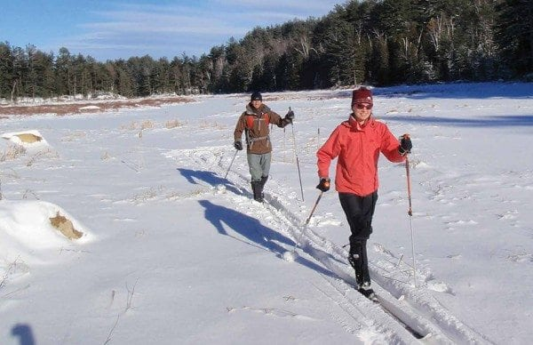 Kim Martineau and Ethan Rouen cross a snowy East Mill Flow. Photo by Phil Brown.
