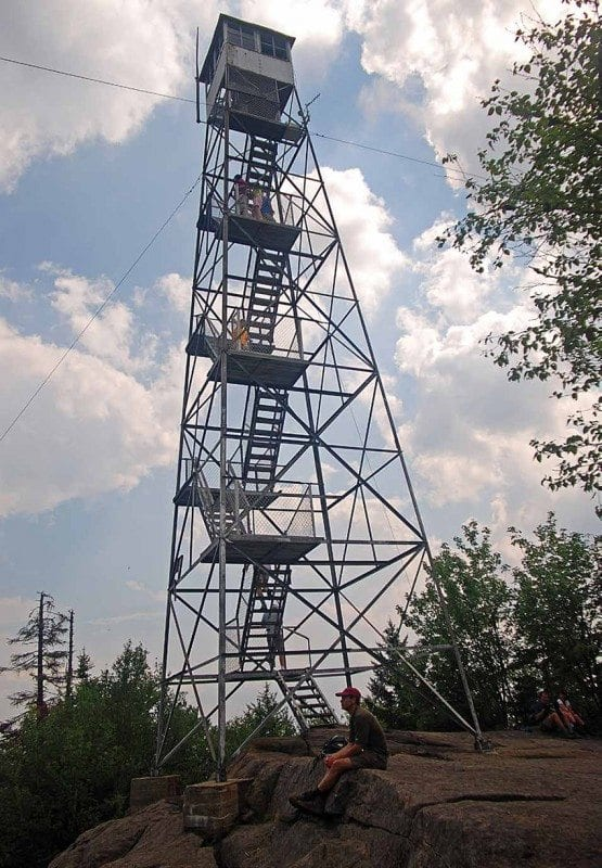 A hiker relaxes beside Goodnow Mountain's restored fire tower. Photo by Lisa Densmore