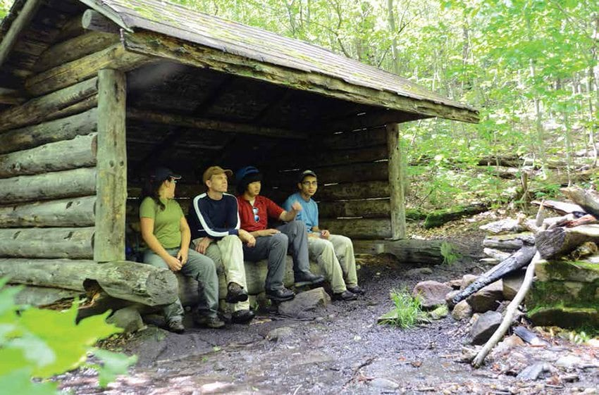 Jack Ballard and his kids relax at a lean-to about three-quarters of a mile below the summit. Photo by Lisa Densmore Ballard