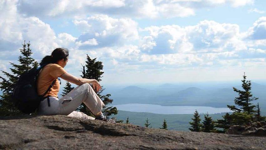 The author gazes down on Meacham Lake from the summit of Debar Mountain. Photo by Jack Ballard