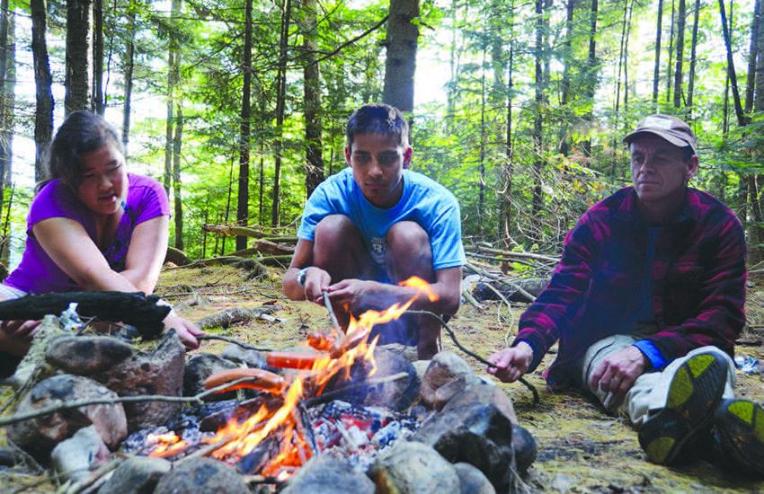 Zoe, Dom, and Jack Ballard roast hotdogs over the campfire. Photo by Lisa Densmore Ballard