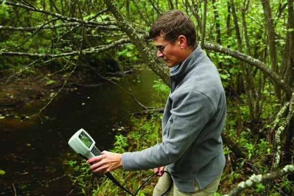 Dan Kelting tests a stream near Paul Smiths for road-salt contamination. Photo by Mike Lynch