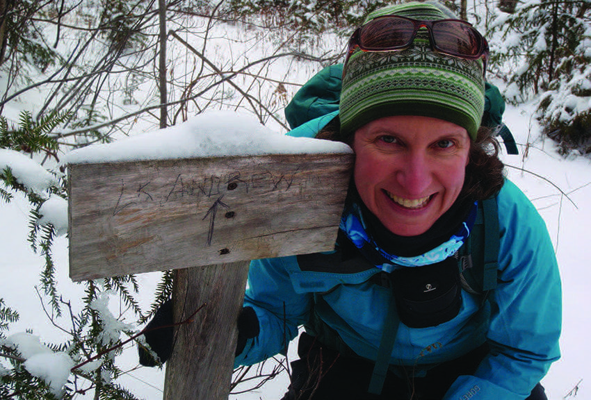 Carol Fox poses near a homemade sign that points the way to Lake Andrew. Photo by Phil Brown