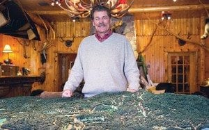 Tom Lawson stands behind a model of the Adirondack Club and Resort. Photo by Mike Lynch