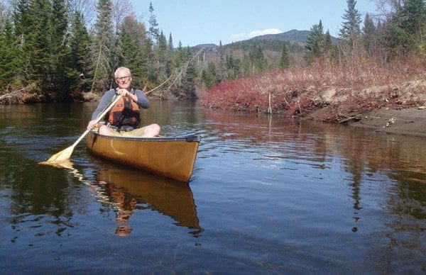 Brian Mann paddles up the Opalescent River, with Allen Mountain looming in the background. Photo by Phil Brown