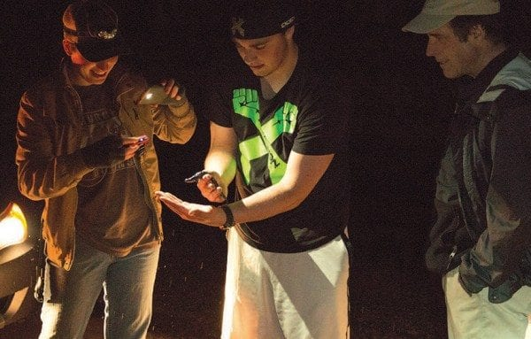 Paul Smith's College students study a spotted salamander during its spring migration this past April, as Professor Curt Stager looks on. Photo by Mike Lynch