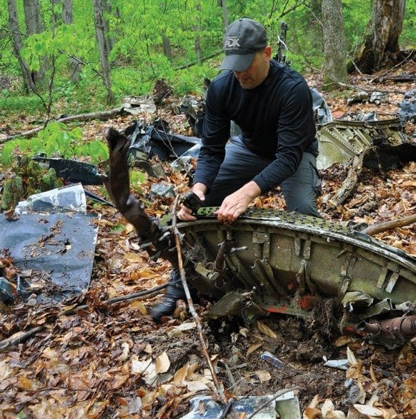 Scott Van Laer grapples with a piece of a Navy plane that crashed in 1945. Photo by Kenneth Aaron