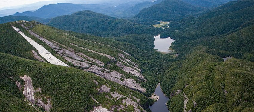 This aerial photo shows Avalanche Lake in the foreground, hemmed in by Mount Colden on the left and Avalanche Mountain on the right. (Tropical Storm Irene create the fresh slide on Colden.) Lake Colden and the Flowed Lands are in the background. Photo by Nancie Battaglia