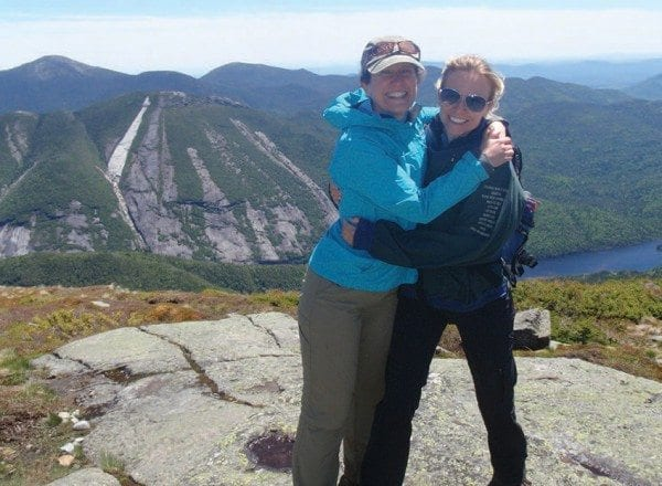 Carol Fox and Emily Lyons celebrate their ascent of Algonquin. The Trap Dike and the new slide on Mount Colden (the white one) can be seen in the background. Photo by Phil Brown