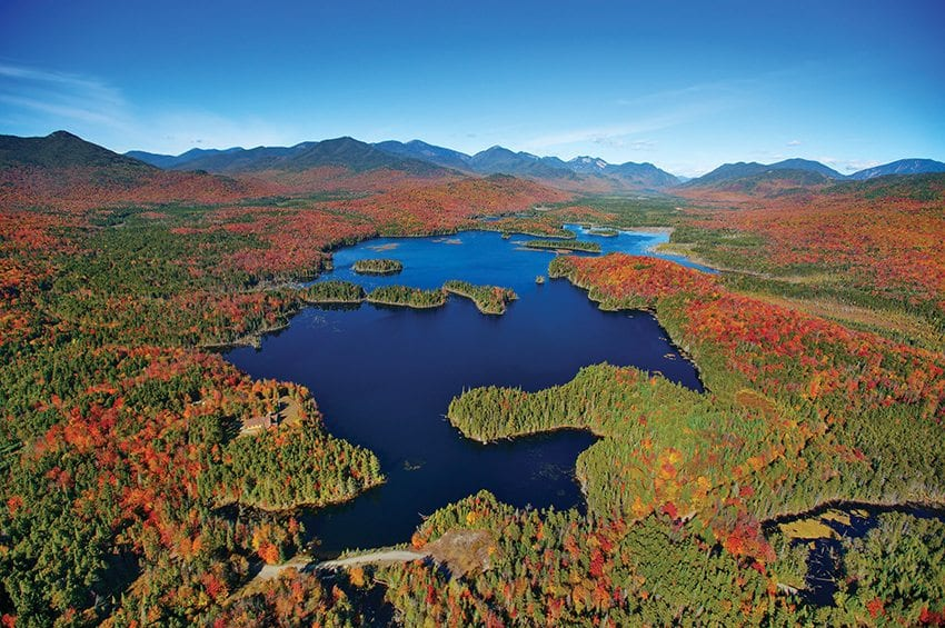 The High Peaks form the backdrop of Boreas Ponds. The state must decide what to do with the lodge and dam visible near the south end of the ponds. Photo by Carl Heilman II/Courtesy of Adirondack Council