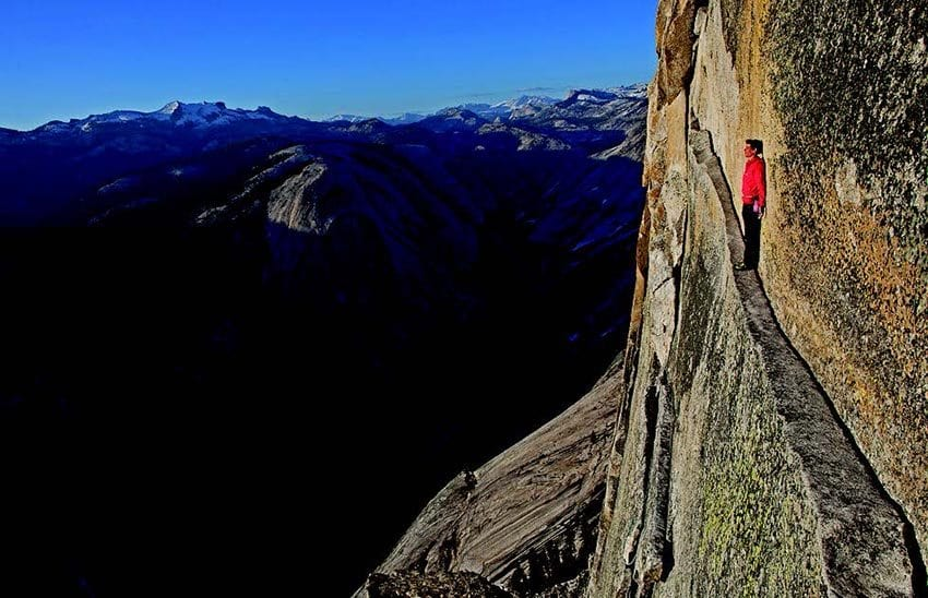 Alex Honnold hangs out on the Thank God Ledge while climbing, without a rope, the North Face of Half Dome in Yosemite National Park. He is about 1,800 feet off the ground. Photo by Jimmy Chin