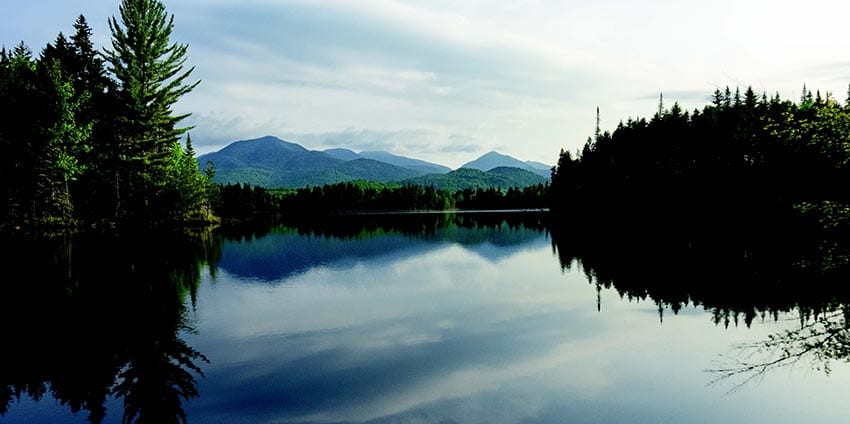 On a still morning, First Pond offers a gorgeous view of the High Peaks. PHOTO BY PHIL BROWN