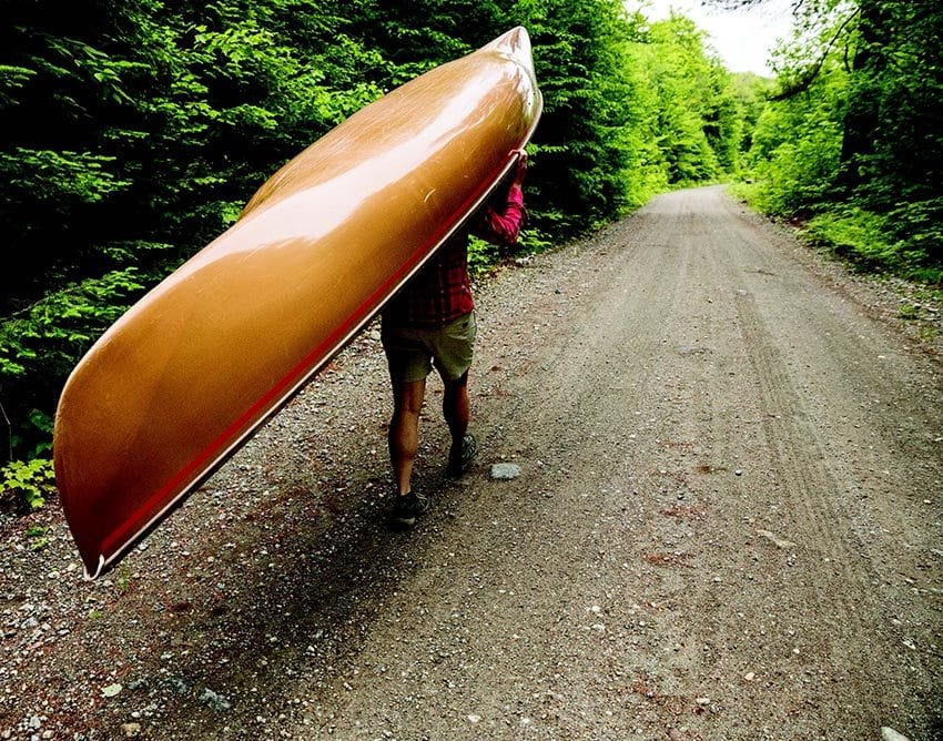 A paddler portages a canoe along Gulf Brook Road. PHOTO BY LISA GODFREY