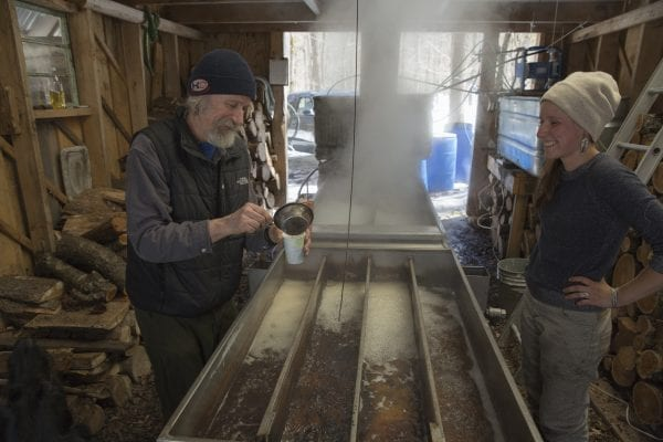 Addison Bickford tests his maple sugar at his sugar shack, as his daughter Celeste looks on.