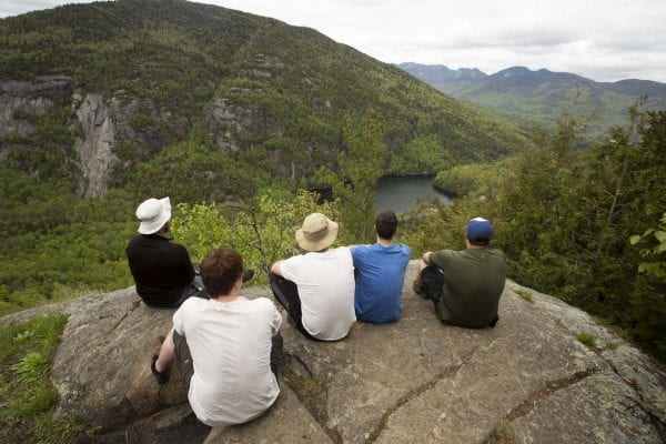 Hikers take in a view of Chapel Pond and nearby cliffs during a hike up Giant Mountain.