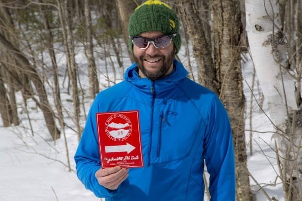 BETA executive director Josh Wilson holds up a Jackrabbit Trail sign in March 2018. Photo by Mike Lynch