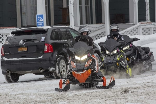 Snowmobilers head back out after a break in Long Lake. Photo by Mike Lynch