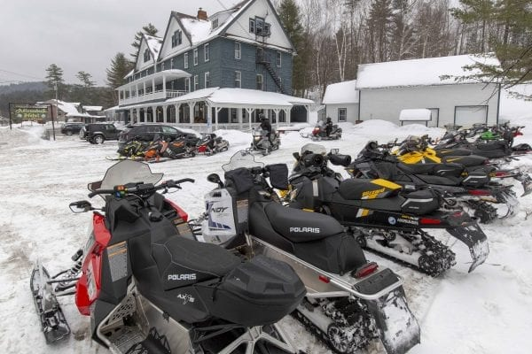 Snowmobiles are lined up outside of the Adirondack Hotel in Long Lake. Photo by Mike Lynch
