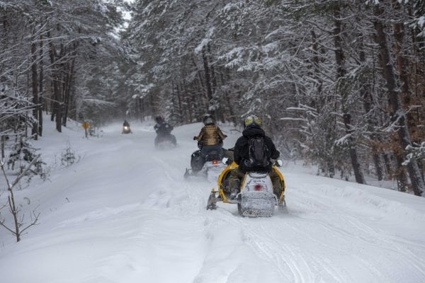Snowmobilers ride the abandoned railroad line through Lake Clear. Photo by Mike Lynch