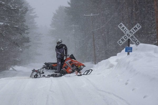 A snowmobiler crosses a road in Lake Clear in Franklin County. Photo by Mike Lynch