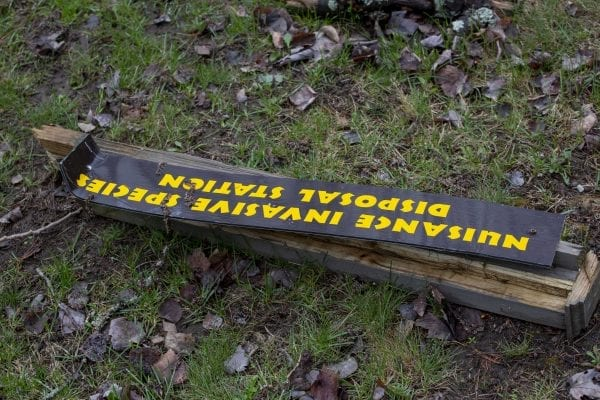 An invasive species sign is seen on the ground at the Crusher boat launch.