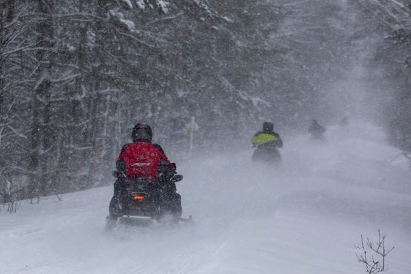 Snowmobilers ride the railroad corridor in Lake Clear. Photo by Mike Lynch