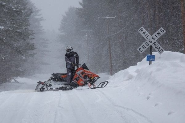 A snowmobiler crosses the road in Lake Clear.  Photo by Mike Lynch