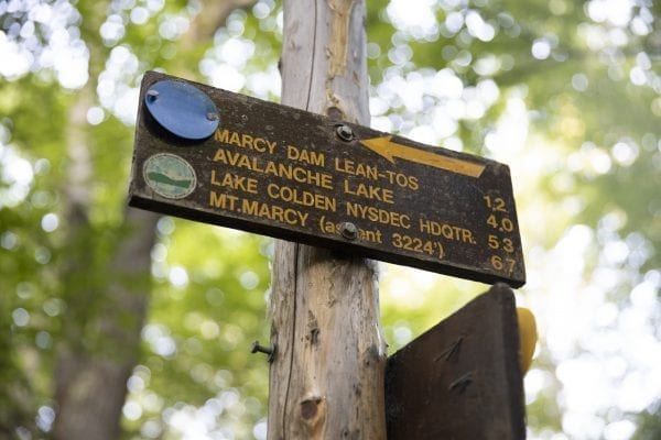A trail sign to Marcy Dam and other popular destinations in the High Peaks. Photo by Mike Lynch