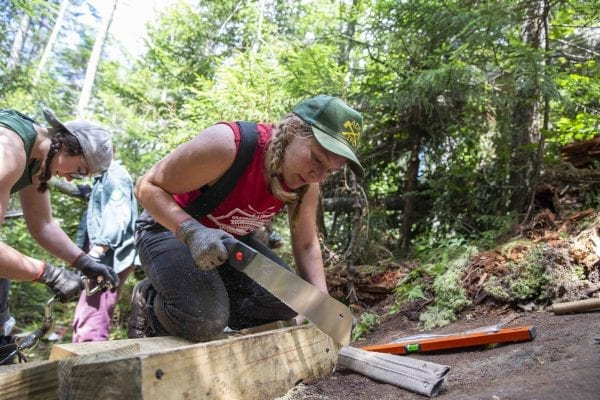 Professional trail crew member Anastasia Rodak works on a ladder going up Mount Colden in late July. Photo by Mike Lynch