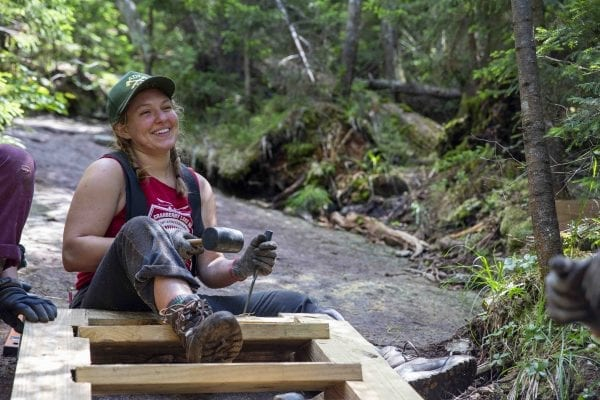 Professional trail crew member Anastasia Rodak enjoys a laugh on Mount Colden. Photo by Mike Lynch