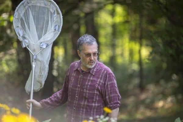 Dan Jenkins looks for monarch butterflies in his garden. Photo by Mike Lynch
