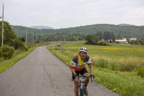 A Cycle Adirondacks participant rides through farmlands in the Champlain Valley. Photo by Mike Lynch