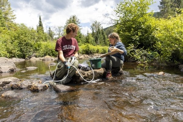 Researchers collect stream water in the High Peaks as part of a brook trout project. The researchers plan to test the water to see if it contains DNA from any trout species. Photo by Mike Lynch