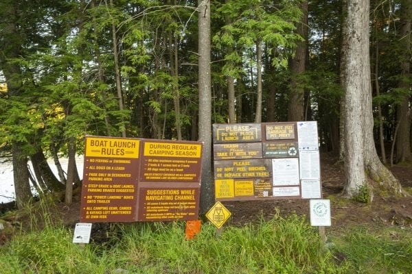 Signs at the Second Pond state boat launch, which provides access to Lower Saranac Lake. Photo by Mike Lynch