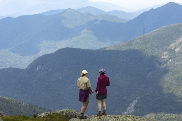 Summit steward Mary Lamb talks with Explorer publisher Tracy Ormsbee on the summit of Mount Marcy. Photo of Mike Lynch