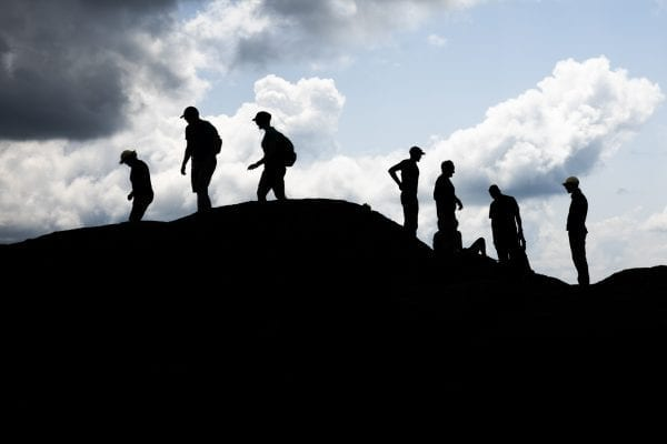 A silhouette of hikers atop Mount Marcy. Photo by Mike Lynch