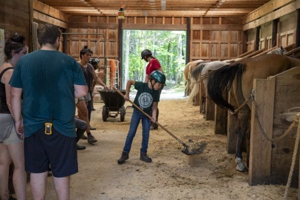 A boy cleans up the stall at Camp Lincoln after riding horses at Camp Lincoln. Photo by Mike Lynch