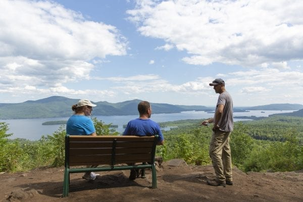 Lake George Land Conservancy land steward Alex Novick talks to hikers on top of Pinnacle Mountain. Photo by Mike Lynch