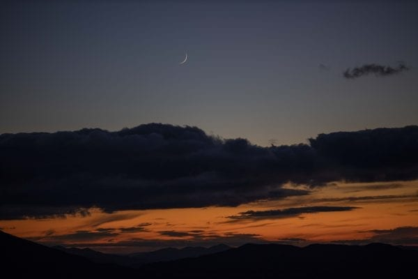A crescent moon in the sky above the sunset and High Peaks was visible from Hurricane Mountain fire tower. Photo by Mike Lynch