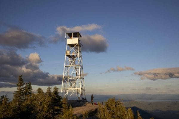 The Hurricane Mountain fire tower lit up by the sun shortly before sunset. Photo by Mike Lynch