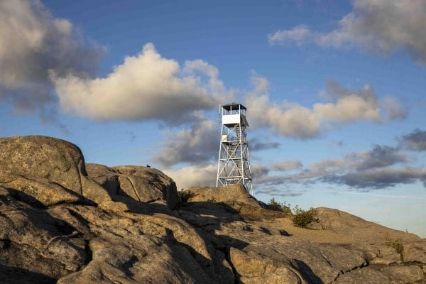 The Hurricane Mountain fire tower lit up by the sun shortly before sunset. The tower is 100 this year. Photo by Mike Lynch